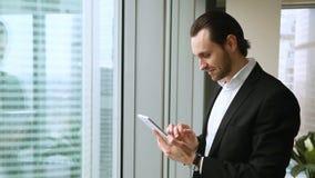 Aantrekkelijke glimlachende zakenman die tablet gebruiken die zich bij venster in bureau bevinden stock video