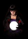 Aantrekkelijke heks of fortuinteller die een kristallen bol onderzoeken Stock Afbeeldingen