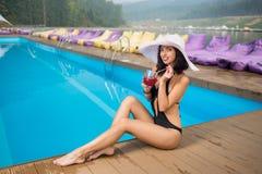 Aantrekkelijke het glimlachen vrouwenzitting met cocktail op de rand van zwembad op de achtergrond van machtig bos royalty-vrije stock foto