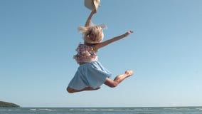Aantrekkelijke het strohoed die van de blondeholding op het strand springen stock video