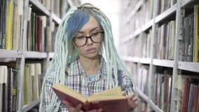 Aantrekkelijke hipster vrouwelijke student in galsses die boek doorbladeren terwijl het bestuderen in bibliotheek met boekenrekac stock video