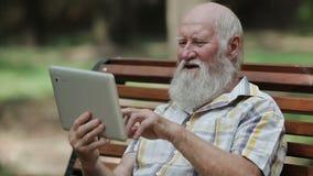 Aantrekkelijke hogere mens die tablet op de bank gebruiken stock video