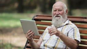 Aantrekkelijke hogere mens die tablet op de bank gebruiken stock videobeelden