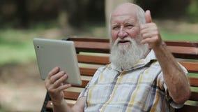 Aantrekkelijke hogere mens die tablet op de bank gebruiken stock footage