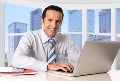 Aantrekkelijke hogere zakenman die in commercieel districtskantoor bij computerlaptop bureau het glimlachen werken Royalty-vrije Stock Foto's
