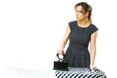 Aantrekkelijke huisvrouw die geruite kleding strijken die uitstekend steenkoolmetaal het strijken hulpmiddel met behulp van stock fotografie