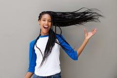 Aantrekkelijke jonge Afrikaanse Amerikaanse vrouw met lang gevlecht haar op grijze achtergrond royalty-vrije stock afbeelding
