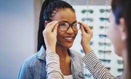 Aantrekkelijke jonge Afrikaanse vrouw die glazen selecteren royalty-vrije stock afbeelding