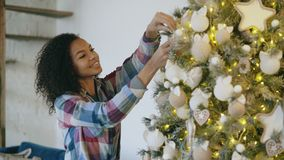 Aantrekkelijke jonge Afrikaanse vrouw die Kerstboom verfraaien die thuis voor Kerstmisviering voorbereidingen treffen royalty-vrije stock foto