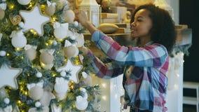 Aantrekkelijke jonge Afrikaanse vrouw die Kerstboom verfraaien die thuis voor Kerstmisviering voorbereidingen treffen royalty-vrije stock afbeelding
