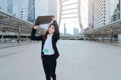 Aantrekkelijke jonge Aziatische bedrijfsvrouw die en ringsbindmiddel lopen opheffen bij stoep van stedelijke stadsachtergrond Stock Afbeeldingen