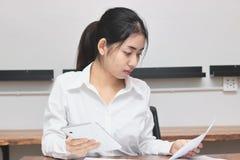 Aantrekkelijke jonge Aziatische onderneemster die aan de werkplaats in bureau werken Het denken en nadenkend bedrijfsconcept stock afbeeldingen