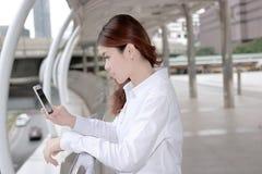 Aantrekkelijke jonge Aziatische vrouw die op mobiele slimme telefoon in haar handen de bouw van stedelijke achtergrond bekijken royalty-vrije stock foto