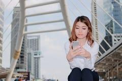 Aantrekkelijke jonge Aziatische vrouw die in wit overhemd mobiele smartphone in haar handen stedelijke de bouwachtergrond bekijkt stock afbeeldingen