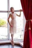 Aantrekkelijke jonge ballerina dichtbij een venster Royalty-vrije Stock Afbeelding
