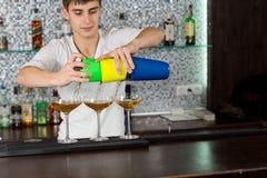 Aantrekkelijke jonge barman die exotische cocktails giet Stock Foto's