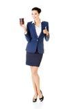 Aantrekkelijke jonge bedrijfsvrouw die een kop houden en o.k. tonen. Stock Afbeeldingen