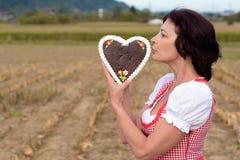 Aantrekkelijke jonge Beierse vrouw die een hart kussen Royalty-vrije Stock Foto's