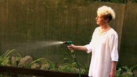 Aantrekkelijke Jonge Blonde het Water geven Tuin stock videobeelden