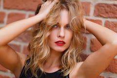 Aantrekkelijke jonge blondevrouw met rode lippen wat betreft haar haar stock fotografie