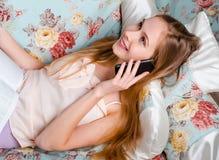 Aantrekkelijke jonge blondevrouw in tansy huis, die op bank i liggen Royalty-vrije Stock Afbeeldingen