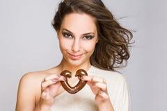 Aantrekkelijke jonge brunette met chocoladehart. Stock Foto