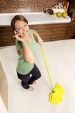 Aantrekkelijke jonge dame die een onderbreking van het schoonmaken neemt stock afbeelding
