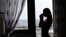 Aantrekkelijke jonge dame die een rust hebben en een kop thee of een koffie voor het venster thuis drinken stock videobeelden