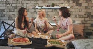 Aantrekkelijke jonge dames in pyjama's die thuis pizza eten en met elkaar babbelen, die over het bed, het glimlachen zitten stock videobeelden