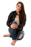 Aantrekkelijke jonge die vrouwenzitting over witte achtergrond wordt geïsoleerd Stock Foto's