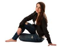 Aantrekkelijke jonge die vrouwenzitting over witte achtergrond wordt geïsoleerd Royalty-vrije Stock Foto