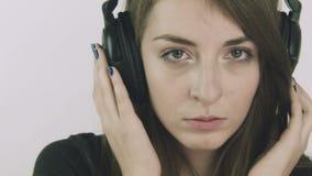Aantrekkelijke jonge droevige vrouw die aan muziek op hoofdtelefoons luisteren stock footage