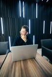 Aantrekkelijke jonge gebaarde mens die in kostuum weg terwijl het zitten bij bureau met laptop en andere punten kijken stock foto