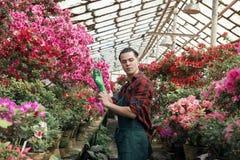 Aantrekkelijke jonge mannelijke tuinman met in kapsel die groene tuinhandschoenen dragen stock fotografie