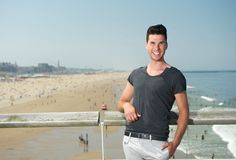Aantrekkelijke jonge mens die bij de kust glimlachen Stock Afbeeldingen