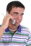 Aantrekkelijke Jonge Mens die bij het Glimlachen Cellphone spreekt Royalty-vrije Stock Afbeeldingen