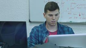 Aantrekkelijke jonge mens die computer met behulp van op zijn werkende plaats Beambte die en Camera glimlachen bekijken stock videobeelden