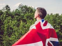 Aantrekkelijke, jonge mens die een Britse Vlag golven stock fotografie