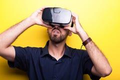 Aantrekkelijke jonge mens die een ontploffing met zijn VR-hoofdtelefoon hebben stock afbeeldingen