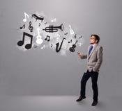Aantrekkelijke jonge mens die en aan muziek met muzikaal zingen luisteren Stock Afbeelding
