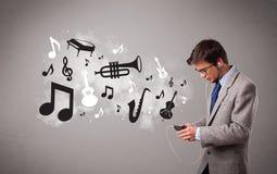 Aantrekkelijke jonge mens die en aan muziek met muzikaal zingen luisteren Royalty-vrije Stock Foto's
