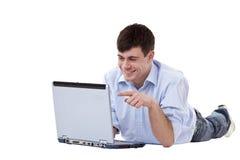 Aantrekkelijke jonge mens die op vloer op computer richt Royalty-vrije Stock Afbeelding