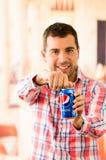 Aantrekkelijke jonge mens die openend een Pepsi-cola glimlachen royalty-vrije stock afbeelding