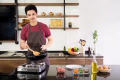 Aantrekkelijke jonge mens die pan en houten spatel houden om omelet voor ontbijt bij moderne keuken in de ochtend te maken Nieuwe royalty-vrije stock fotografie