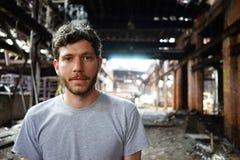Aantrekkelijke jonge mens die zich openlucht voor verlaten huis, die camera bekijken bevinden Foto in Detroit, Michigan wordt gen stock foto