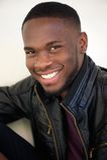 Aantrekkelijke jonge mens die in zwart leerjasje glimlachen Royalty-vrije Stock Afbeelding