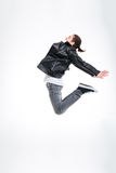 Aantrekkelijke jonge mens die in zwart leerjasje hoog springen Stock Fotografie