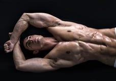 Aantrekkelijke jonge mens op de vloer met spier gescheurd lichaam Stock Foto's