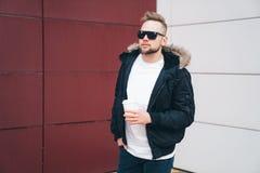 Aantrekkelijke jonge mens in toevallige clothers met koffie in zijn handen die zich op de bureaubouw achtergrond bevinden stock afbeelding