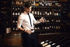 Aantrekkelijke jonge mens in wit kostuum en broeken die rode wijn degustating royalty-vrije stock fotografie